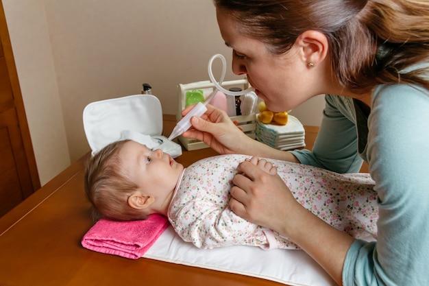 Мать использует назальный аспиратор для очистки носа ребенка