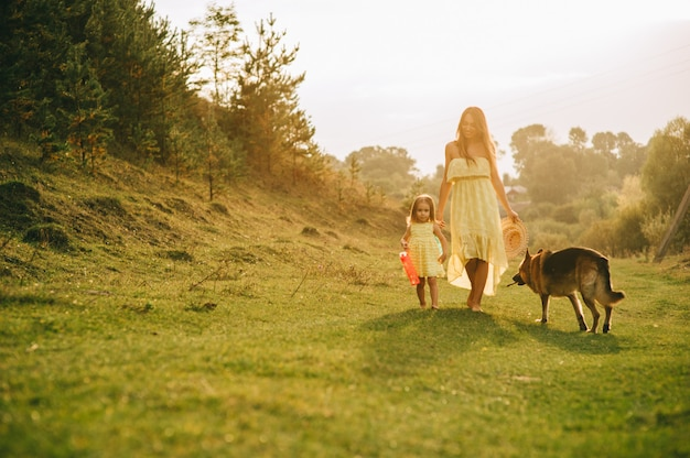 Mother walk with his little daughter, and their dog