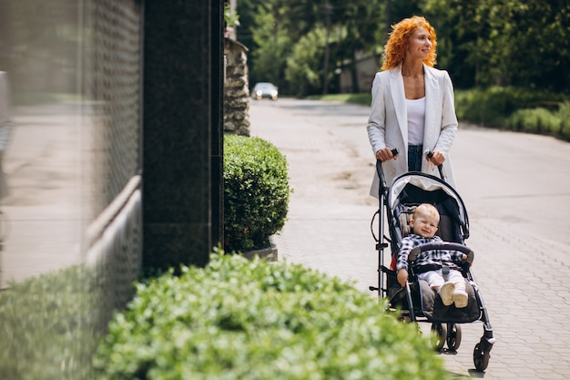 Mother walking by the house with her little son in a baby carriage