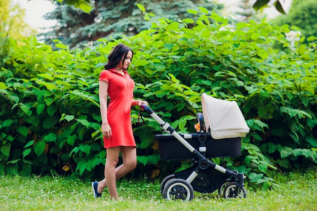 Mother walking with baby pram stroller, carriage in town. love and family concept.