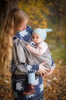 屋外で子供と一緒に歩く母親、スリングでのベビースリング