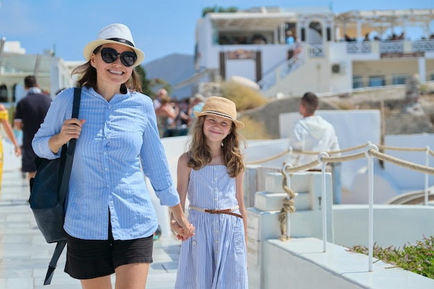 Mother walking with daughter child holding hand in famous tourist village oia santorini island