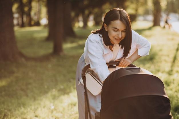 公園で彼女の赤ん坊の娘と一緒に歩いている母