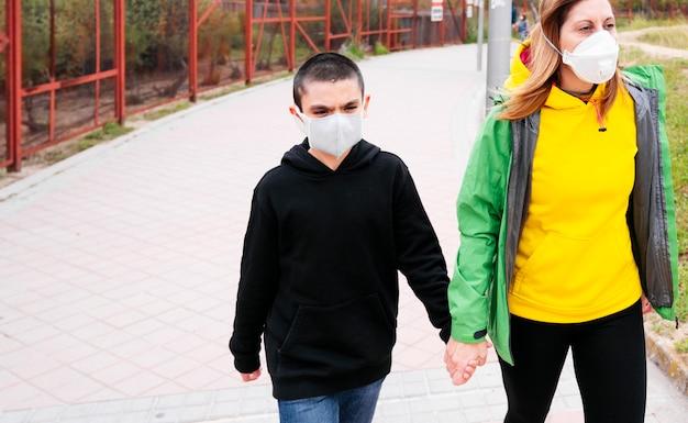 路上で息子と一緒に歩く母