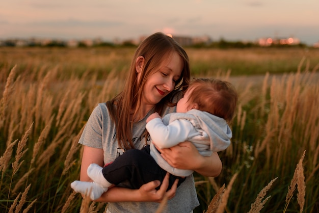 A mother walks in the field with her little daughter in her arms.