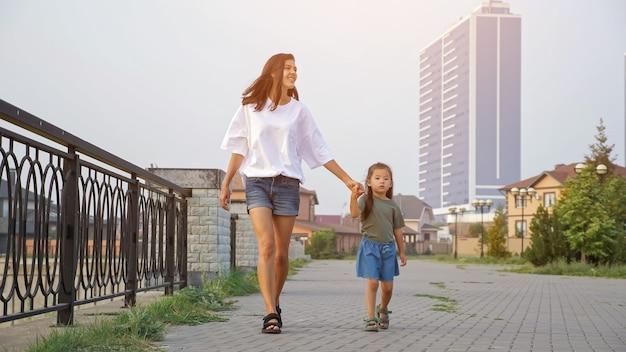 Мать гуляет с корейской маленькой девочкой по набережной