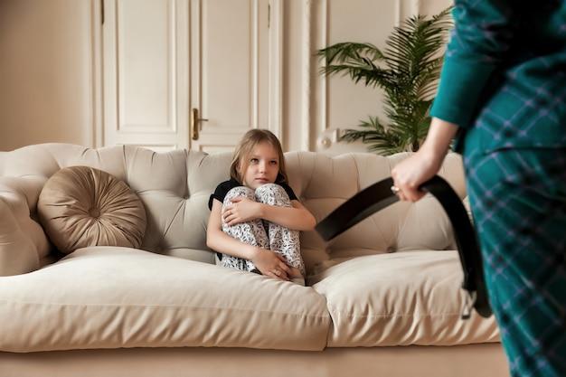 母は手にベルトを持って子供を罰したいと思っています。怒ったお母さんは娘を怒らせて罰し、赤ちゃんをベルトで殴ります。家族の喧嘩問題と子育ての概念