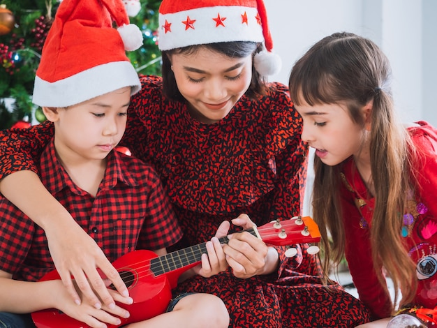 Mother was playing the guitar on christmas day with boy and girl