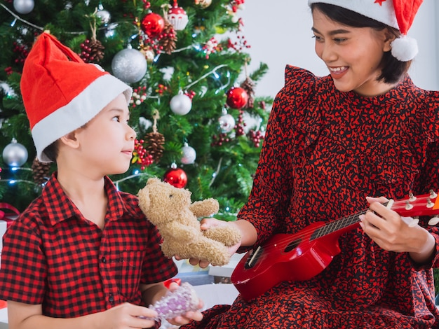 Mother was playing the guitar on christmas day with boy