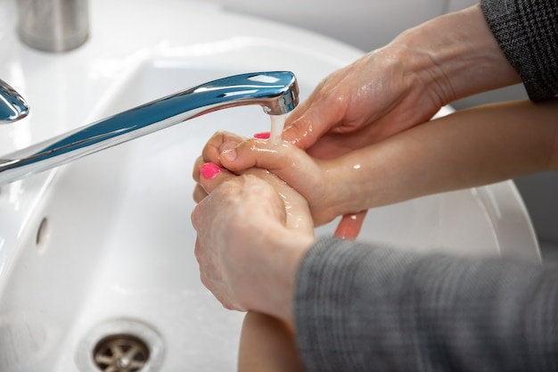 Mother washing hands her son carefully in bathroom close up prevention of infection and pneumonia virus spreading