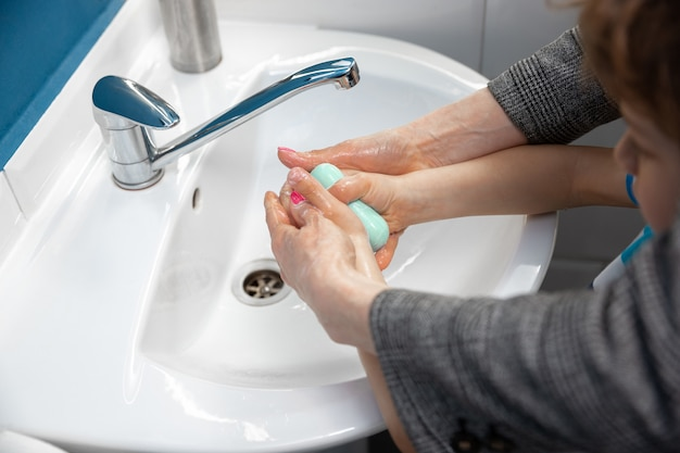 Mother washing hands her son carefully in bathroom close up. prevention of infection and pneumonia virus spreading