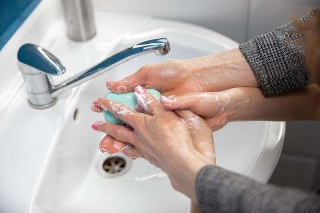 Мать тщательно моет руки своему сыну в ванной комнате крупным планом, предотвращая распространение вируса пневмонии и инфекции