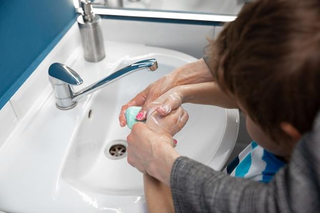 バスルームで息子の手を洗う母親をクローズアップ。感染の予防と肺炎ウイルスの蔓延