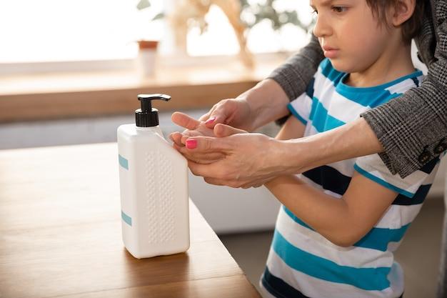 욕실에서 조심스럽게 그녀의 아들 손을 씻는 어머니를 닫습니다. 감염 예방