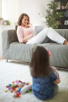 La madre guarda il video su un tablet mentre la sua piccola figlia gioca con i giocattoli sul tappeto