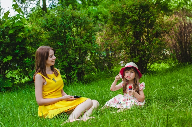 Mother watching as her daughter blows soap bubbles
