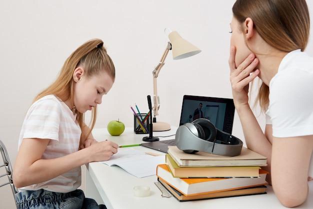 Мать смотрит, как ее дочь делает домашнее задание на ноутбуке дома
