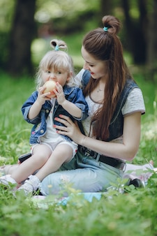 Mother watching her daughter while eating an apple