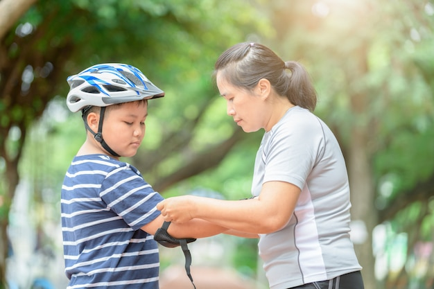 Mother wear elbow protection to his son