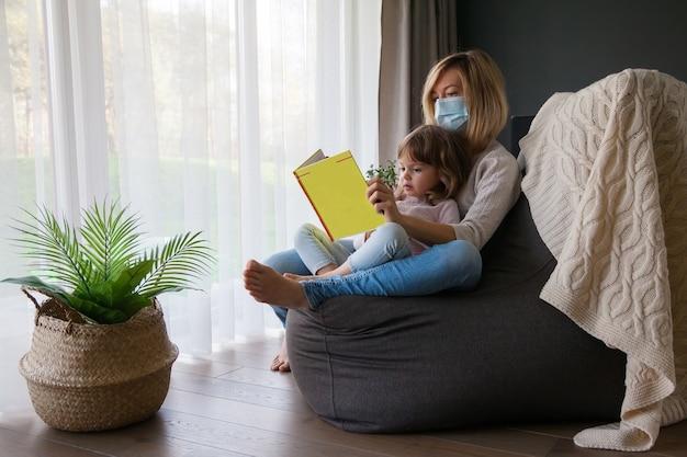 Мать в маске для лица и читает ребенку