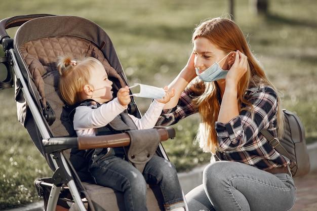 얼굴 마스크를 착용하는 어머니. 야외에서 산책하는 유행병 동안 아기 유모차와 엄마.