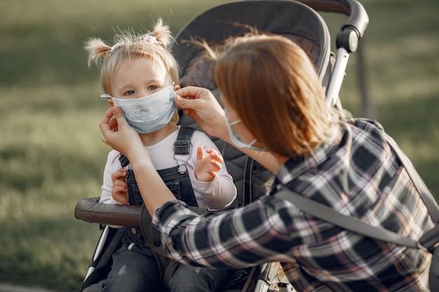 フェイスマスクを着用した母親。パンデミックの最中にベビーカーを持ったお母さんが屋外を散歩しています。