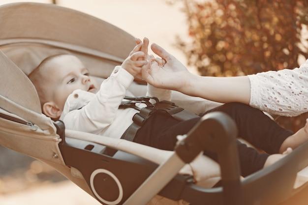 얼굴 마스크를 착용하는 어머니. 여자는 벤치에 앉아입니다. 야외에서 산책하는 유행병 동안 아기 유모차와 엄마.