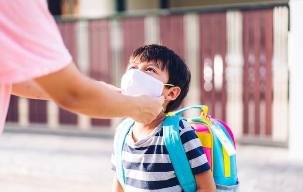 코로나바이러스에 대비해 어린 아시아 소년 아들을 위해 보호 마스크를 쓴 어머니는 학교로 돌아갈 준비를 하고 있다