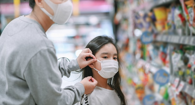 Mother wearing a protective mask puts a face mask on a daughter in supermarket