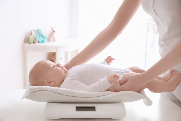 部屋の体重計で赤ちゃんに重みを付ける母親