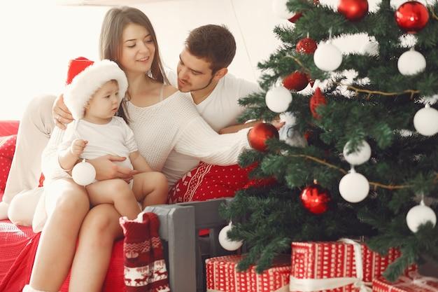 Madre in un maglione bianco. famiglia con regali di natale. bambino con i genitori in decorazioni natalizie.