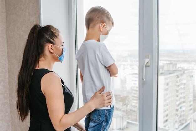 의료 마스크에 아이를 가진 어머니는 격리에서 집에 앉아 있고 창 밖을 봐. 코로 노 바이러스 및 코 비드 예방 -19