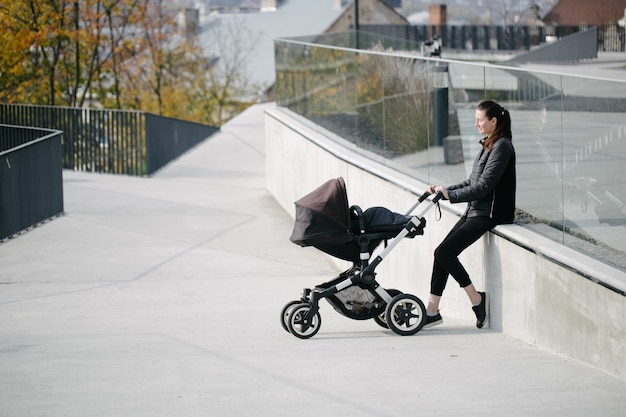 現代の街の通りで乳母車やベビーカーを持った母親