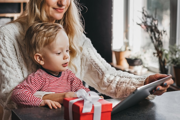 小さな子供を持つ母親はタブレットを持って、新年とクリスマス休暇のためにインターネットでオンライン購入をします