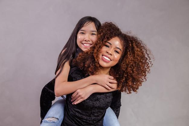 Мать с приемной дочерью на сером фоне. черная мать с японской дочерью. концепция усыновления