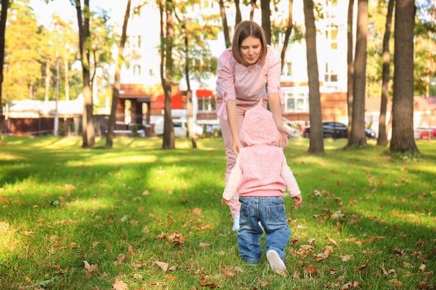 Мать с очаровательной маленькой девочкой, играя вместе в осеннем парке