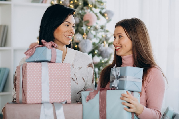 Mother with adult daughter with christmas presents by christmas tree