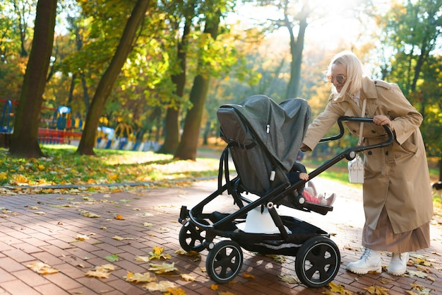 Mother with baby carriage walking in autumn park