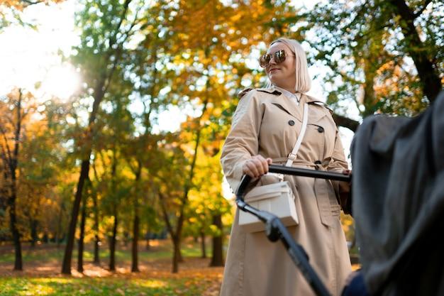 Мать с детской коляской, прогулки в парке