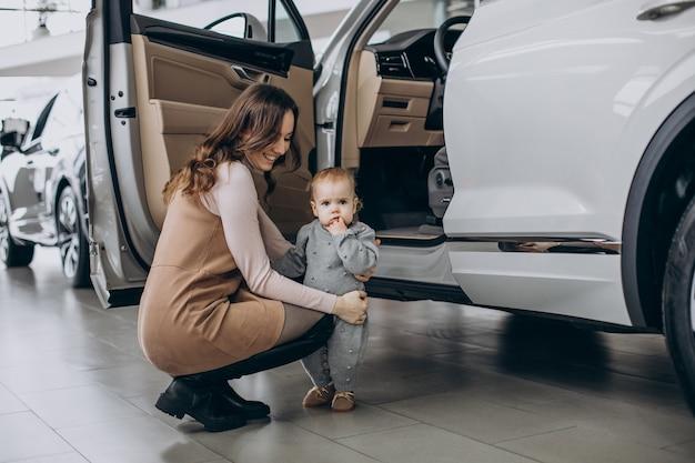 車を選ぶ赤ん坊の娘を持つ母親