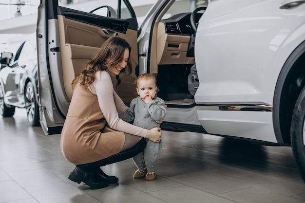 Mother with baby daughter choosing a car
