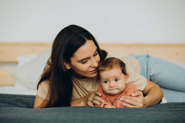 Mother with baby daughter lying on bed