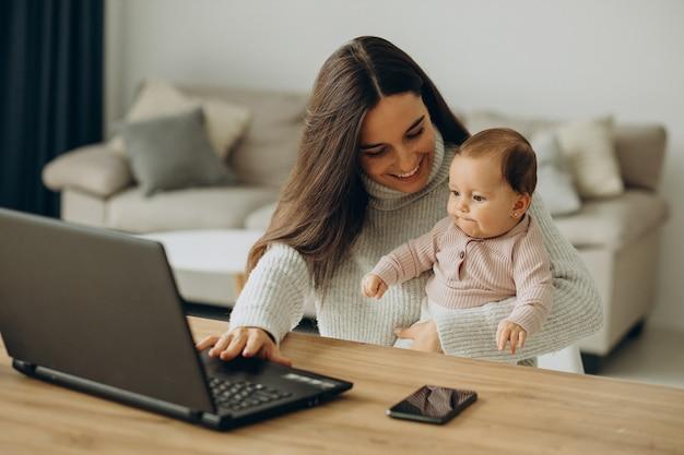 自宅からコンピューターで作業している赤ん坊の娘を持つ母