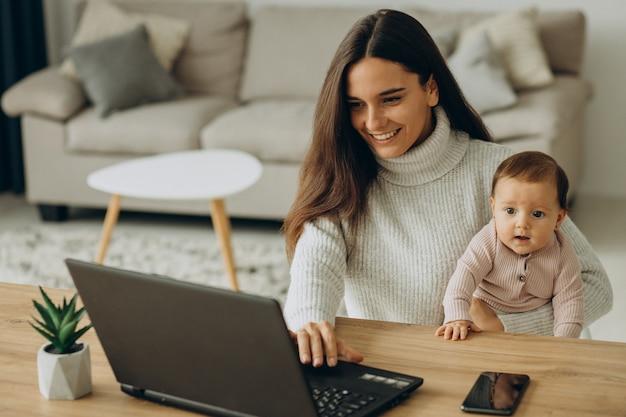 집에서 컴퓨터 작업을 하는 아기 딸을 둔 어머니