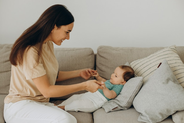 自宅のソファで女の赤ちゃんを持つ母親