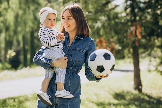 公園でボールで遊ぶ女の赤ちゃんを持つ母