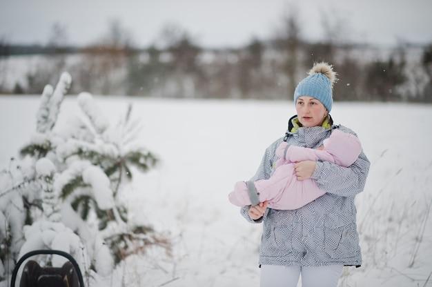 冬の日に女の赤ちゃんの幼児を持つ母親。