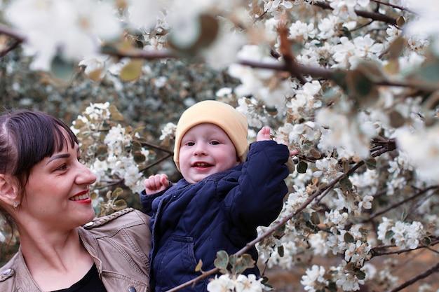 Мать с младенцем в летнем саду солнечный день лесное дерево