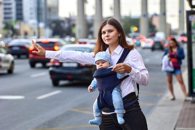 Мать с младенцем в слинге останавливает такси возле пробок