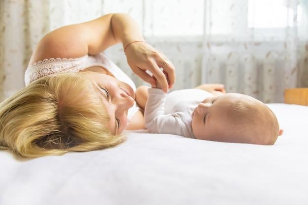 Мать с младенцем, лежа на кровати